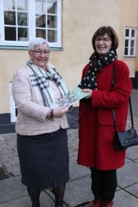 Kulturudvalgsformand Anette Simoni nåede akkurat ikke gruppebilledet og får overrakt Køge Studier direkte af Museums- og Arkivleder Birte Broch