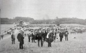 Fra Folkemødet på Ølby Ås 1887. Vejen til venstre er Bondestævnet, huset i baggrunden er Danehøjhuset set fra nord. Fotografi fra Højelse Sognearkiv (B576).